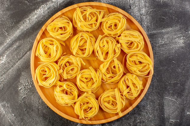 Top view shaped italian pasta in flower form raw and yellow on the wooden desk italian raw food meal spaghetti