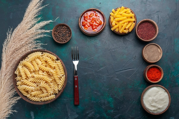 Top view shaped italian pasta with different seasonings on dark blue background