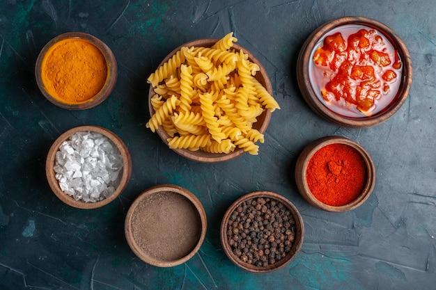 Vista dall'alto a forma di pasta italiana con diversi condimenti sulla scrivania blu scuro