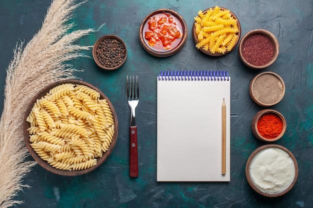 濃い青の背景にメモ帳とさまざまな調味料を使った上面図の形をしたイタリアンパスタ