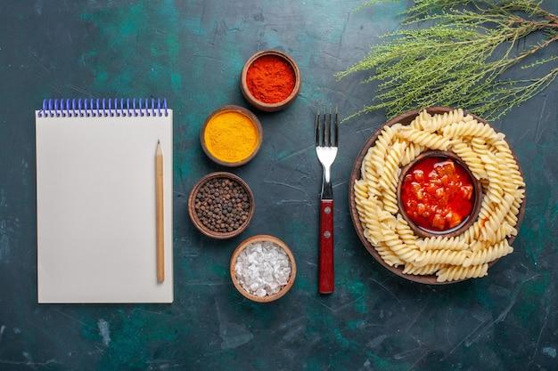 濃紺の背景にメモ帳と調味料を使った上面図の形をしたイタリアンパスタ