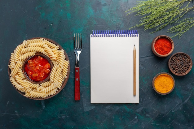 Top view shaped italian pasta with notepad and different seasonings on dark blue background