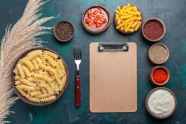 Pasta italiana a forma di vista dall'alto con blocco note e diversi condimenti su sfondo blu scuro