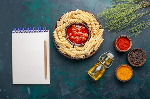 Top view shaped italian pasta with oil notepad and different seasonings on dark blue background
