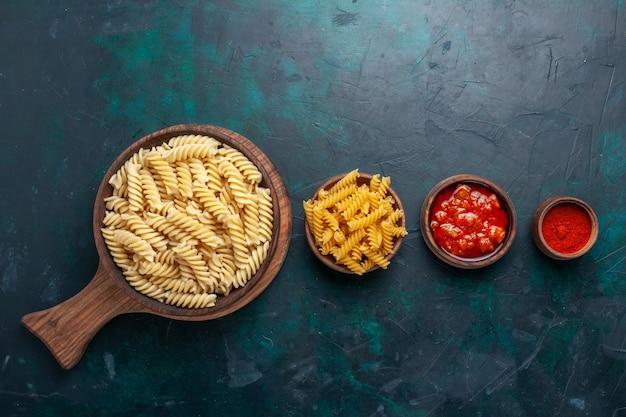 紺色の机の上にソースと調味料を添えた上面図の形をしたイタリアンパスタ
