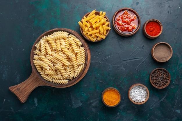 Vista dall'alto a forma di pasta italiana con salsa e condimenti diversi sulla scrivania blu scuro