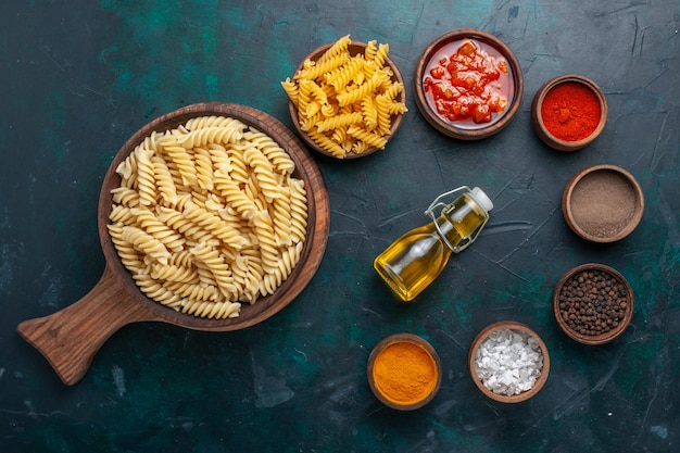 Top view shaped italian pasta with sauce and seasonings on dark-blue desk