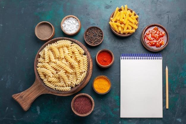 Vista dall'alto a forma di pasta italiana con condimenti sulla scrivania blu scuro