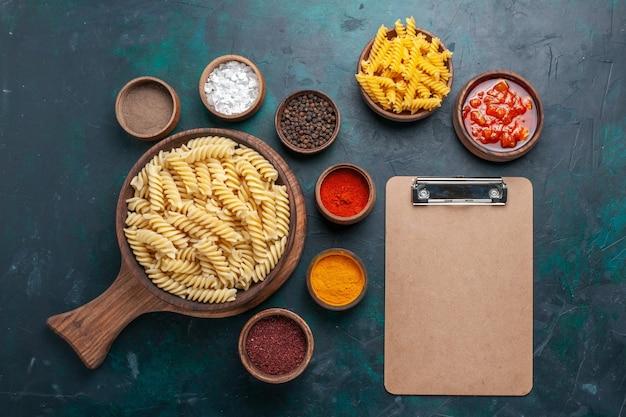 Top view shaped italian pasta with seasonings on dark blue desk