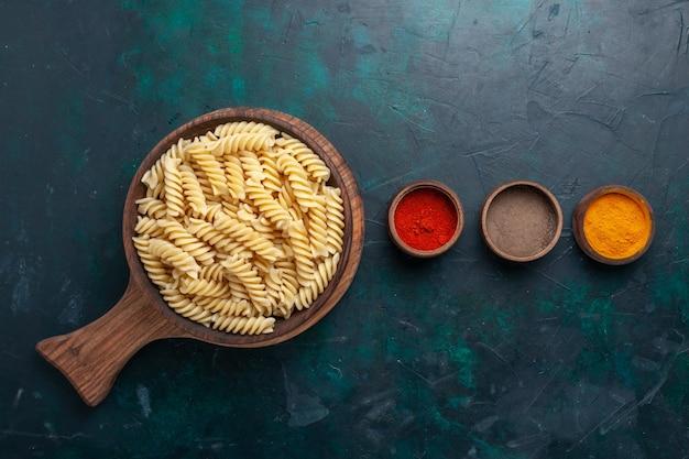 Вид сверху итальянской пасты с приправами на темно-синем столе