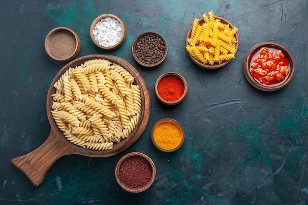 紺色の机の上に調味料を入れた上面図の形をしたイタリアンパスタ