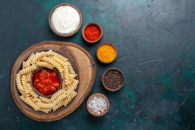 ダークブルーの背景にトマトソースと調味料を添えた上面図の形をしたイタリアンパスタ