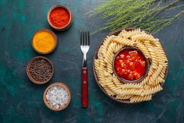 Вид сверху в форме итальянской пасты с томатным соусом и приправами на темно-синем фоне