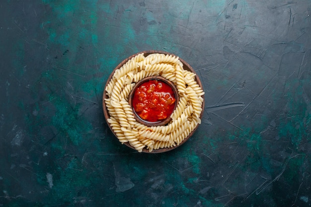 Vista dall'alto a forma di pasta italiana con salsa di pomodoro sulla scrivania blu scuro