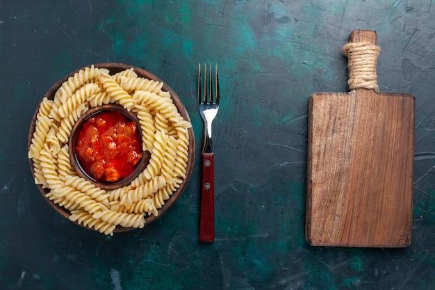 Vista dall'alto a forma di pasta italiana con salsa di pomodoro e scrivania su sfondo blu scuro