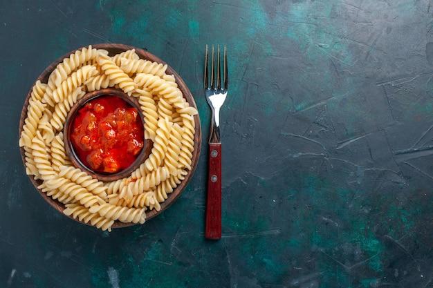 紺色の机の上にトマトソースを添えた上面図の形をしたイタリアンパスタ