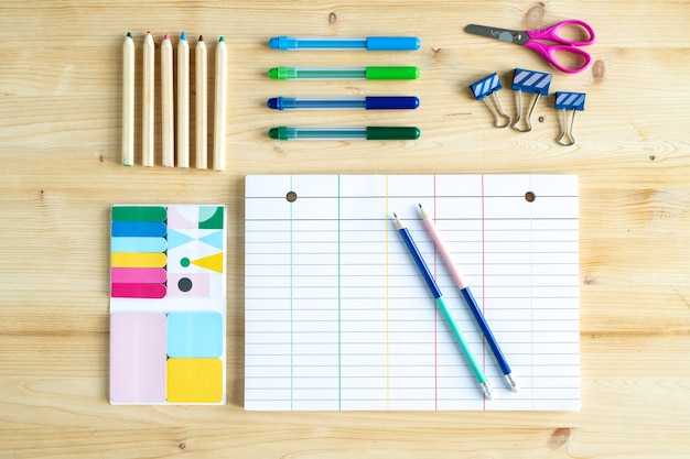 Top view of sheet of paper with lines surrounded by group of pencils and crayons with clips, scissors and set of erasers