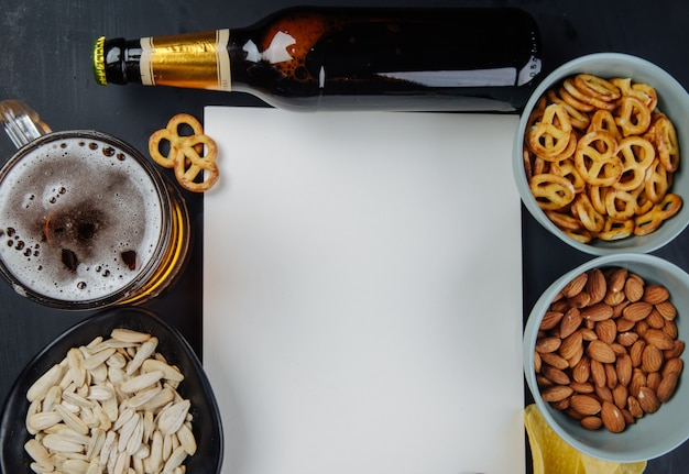 Top view of a sheet of white paper and a bottle of beer with varied beer snacks and a mug of beer on black