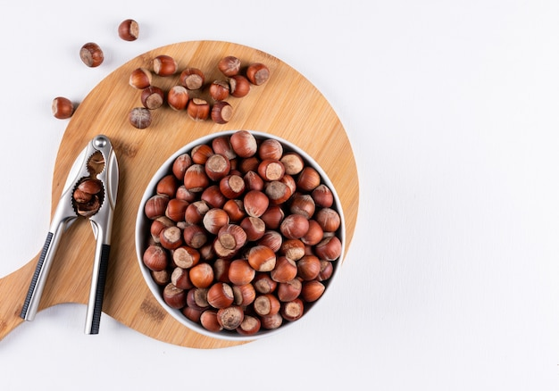 Top view shelled hazelnuts in white bowls with nutcracker on wooden cutting board
