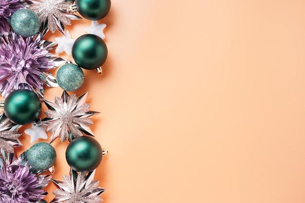 Вид сверху на блестящие и красочные рождественские украшения и безделушки, размещенные на левом краю кадра. концепция праздника и празднования для открыток с копией пространства