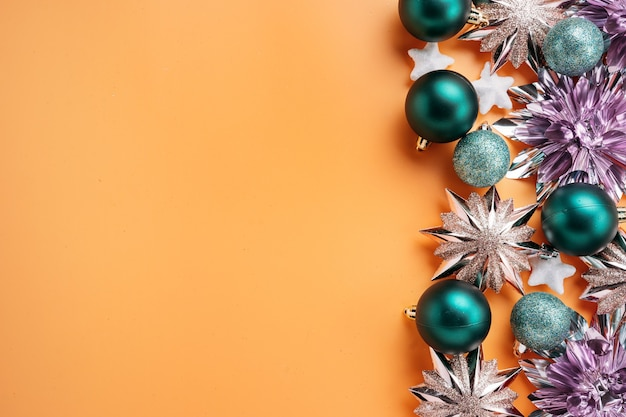 Вид сверху, блестящие и красочные зеленые и розовые рождественские украшения и безделушки, размещенные на правом краю кадра. концепция праздника и празднования для открыток с копией пространства