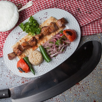 Top view shish kebab with fried vegetables and chopped onion and ayran and knife in white plate