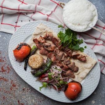 Vista dall'alto shish kebab con pomodoro e cipolla e ayran