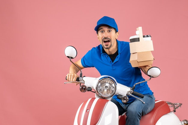 Top view of shocked courier guy in medical mask wearing hat sitting on scooter holding order on pastel peach background