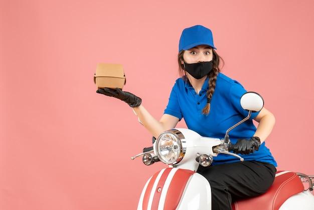 Vista dall'alto del fattorino scioccato che indossa maschera medica e guanti seduto su uno scooter che consegna ordini su sfondo color pesca pastello