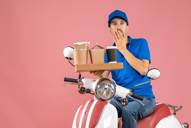Top view of shocked emotional courier man wearing hat sitting on scooter on pastel peach background