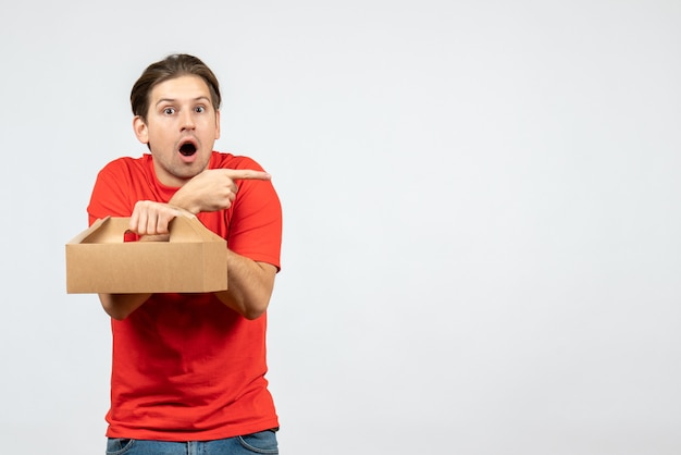 Vista dall'alto del giovane scioccato ed emotivo in camicia rossa che tiene la scatola che indica qualcosa sul lato sinistro su sfondo bianco
