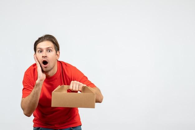 Vista dall'alto del giovane scioccato ed emotivo in camicetta rossa che tiene scatola su sfondo bianco