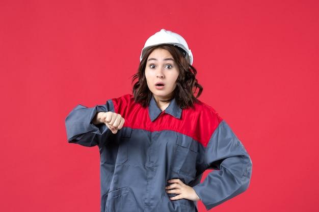 Vista dall'alto del costruttore femminile scioccato in uniforme con elmetto e che controlla il suo tempo su sfondo rosso isolato