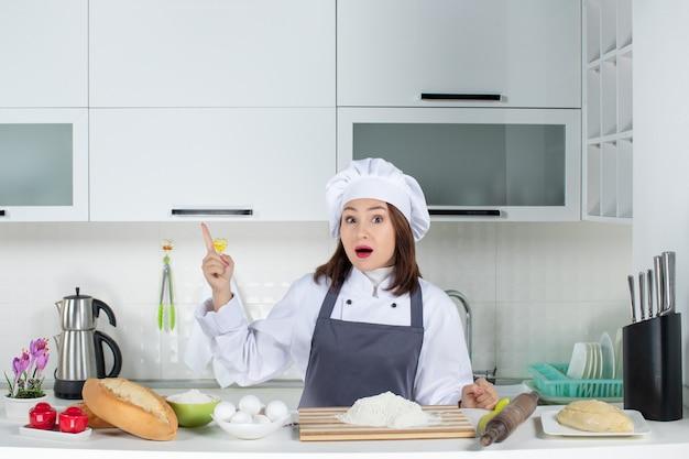 Vista dall'alto della chef donna scioccata in uniforme in piedi dietro il tavolo con le verdure del pane del tagliere che puntano verso l'alto nella cucina bianca
