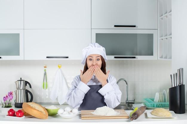 Vista dall'alto della chef donna scioccata in uniforme in piedi dietro il tavolo con tagliere di pane e verdure nella cucina bianca