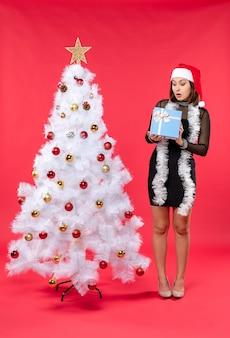 Vista dall'alto della ragazza scioccata in un vestito nero con il cappello di babbo natale in piedi vicino all'albero di natale e tenendo il regalo di capodanno sul rosso
