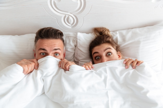 Top view of shocked lovely couple lying together in bed