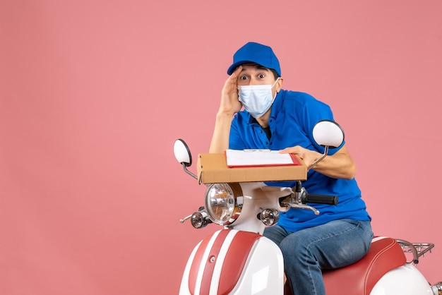 Top view of shocked male delivery person in mask wearing hat sitting on scooter delivering orders holding document on peach background