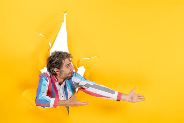 Vista dall'alto di un giovane scioccato che guarda qualcosa sul lato sinistro attraverso un buco strappato in carta gialla