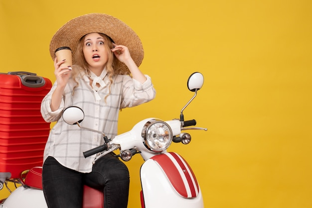 Top view of shocked young woman wearing hat and sitting on motorcycle and holding coffee