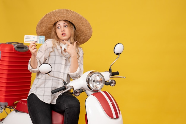 Top view of shocked young woman wearing hat and sitting on motorcycle and holding ticket on yellow