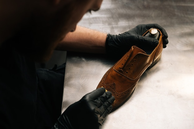 Top view of shoemaker wearing black latex gloves cleaning old light brown leather shoes with rag