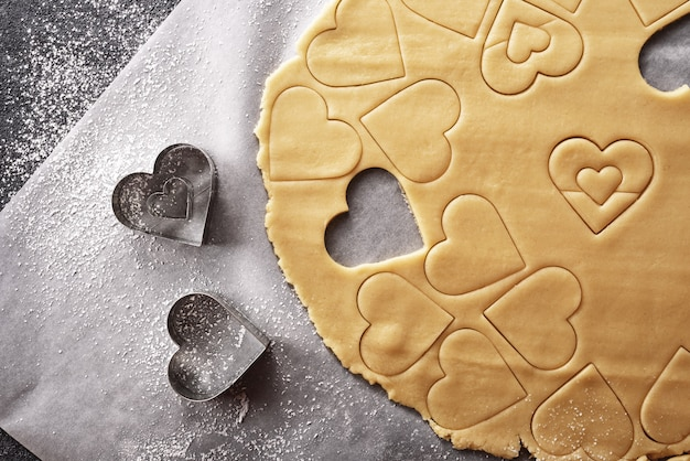 Top view of shortcake dough with heart shapes on grey background