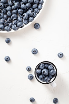 Top view shot of blueberries in a mug and on a white plate on  white surface