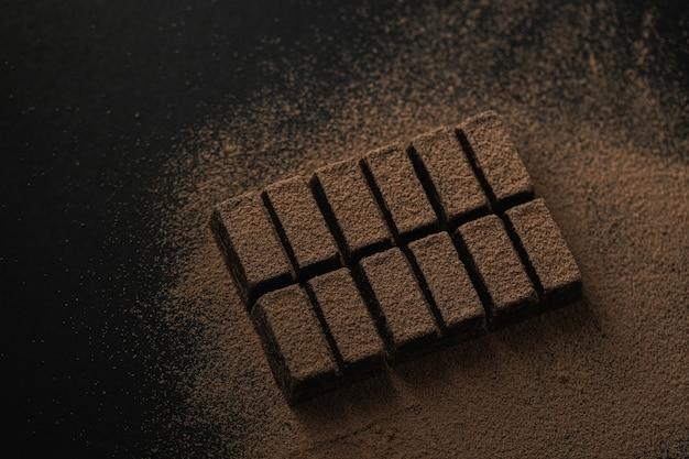 Vista dall'alto di una barretta di cioccolato fondente cosparsa di cacao in polvere