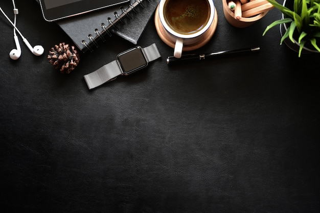 Top view shot of dark leather business desktop with office gadget and copy space