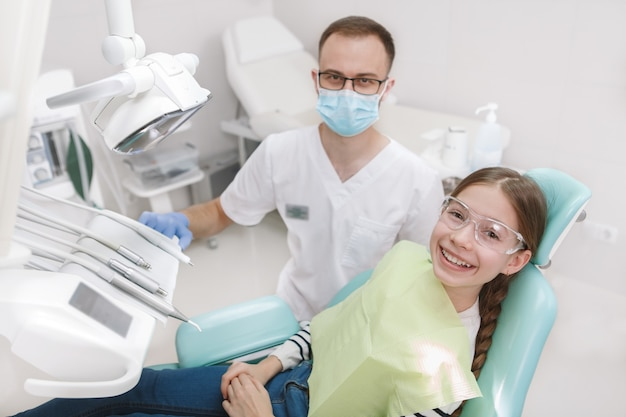 Top view shot of a dentist at his young patient in dental chair