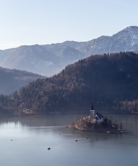 Top view shot of a hill straza and a small island in the middle of a lake bled in bled, slovenia