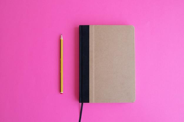 Снимок бежевого ежедневника и желтой ручки на розовом фоне, вид сверху