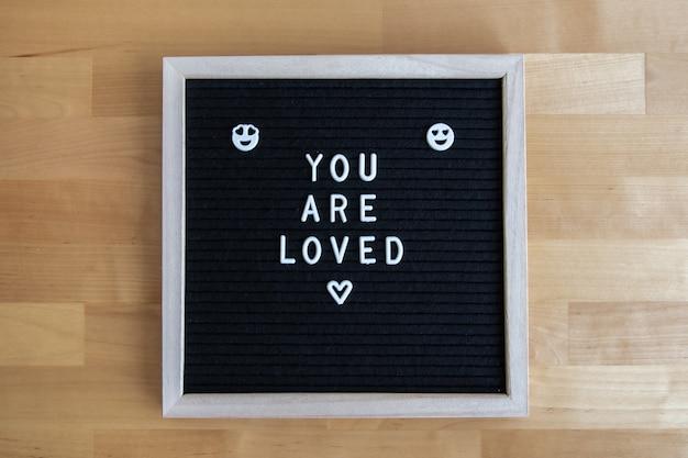 あなたと一緒に木製のテーブルの上の黒い空のボードの平面図のショットは、引用が大好きです